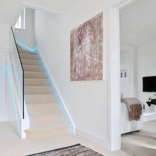 На фото: большие п-образные лестницы в современном стиле с ступенями с ковровым покрытием, стеклянными подступенками и стеклянными перилами