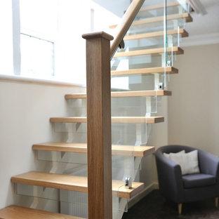 カーディフの中サイズの木のコンテンポラリースタイルのおしゃれなかね折れ階段 (ガラスの蹴込み板、木材の手すり) の写真