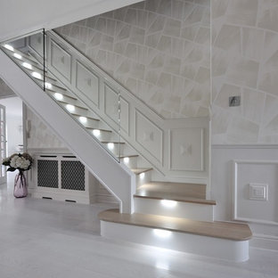 Inspiration for a large contemporary wooden curved glass railing staircase remodel in London with glass risers