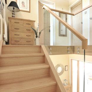 """Esempio di una scala a """"U"""" design di medie dimensioni con pedata in legno, alzata in vetro e parapetto in legno"""