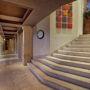 Large world-inspired curved staircase in Hawaii with limestone treads and limestone risers.