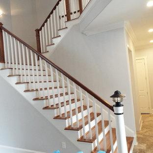 Exempel på en stor modern u-trappa i trä, med räcke i trä och sättsteg i målat trä