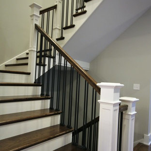 This is an example of a large industrial wood u-shaped metal railing staircase in Chicago with painted wood risers.