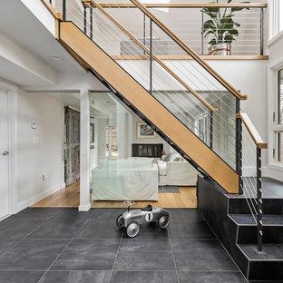 Ejemplo de escalera en L, contemporánea, de tamaño medio, sin contrahuella, con barandilla de cable y escalones de madera