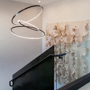 オレンジカウンティの広い金属製のコンテンポラリースタイルのおしゃれなかね折れ階段 (木の蹴込み板、金属の手すり) の写真
