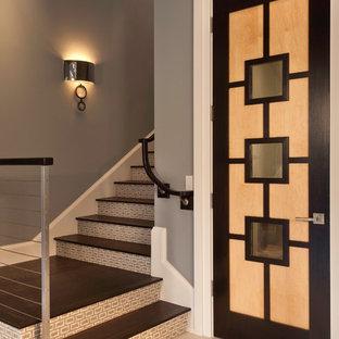 Imagen de escalera contemporánea con escalones de madera y contrahuellas con baldosas y/o azulejos