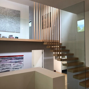 Photo of a contemporary wood u-shaped staircase in Canberra - Queanbeyan with open risers and glass railing.