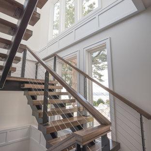 ニューヨークの木のコンテンポラリースタイルのおしゃれな折り返し階段 (金属の蹴込み板、木材の手すり) の写真