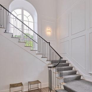 Diseño de escalera en U y boiserie, clásica renovada, grande, con escalones enmoquetados, contrahuellas enmoquetadas, barandilla de metal y boiserie