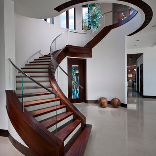Staircase - contemporary wooden curved glass railing staircase idea in Miami with painted risers