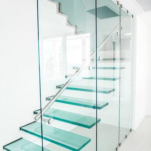 Immagine di una scala sospesa minimal con pedata in vetro, nessuna alzata e parapetto in vetro