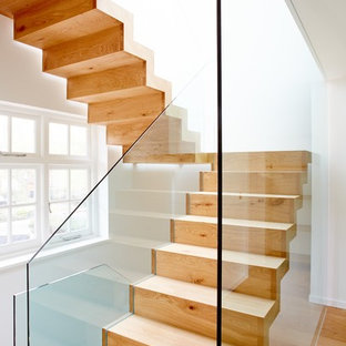 Contemporary wood straight glass railing staircase in London with wood risers.