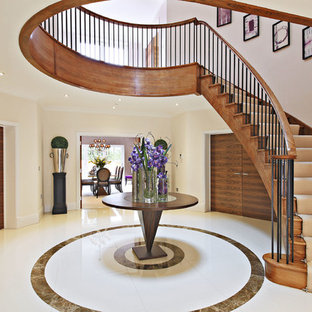 Large contemporary wood curved staircase in London with wood risers.