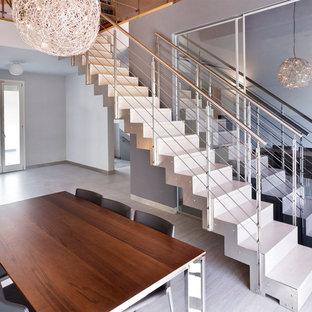 Стильный дизайн: прямая лестница в современном стиле с металлическими подступенками, перилами из тросов и металлическими ступенями - последний тренд