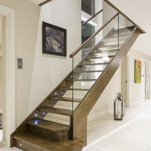 ハンプシャーの中サイズの木のコンテンポラリースタイルのおしゃれな直階段 (ガラスの蹴込み板、混合材の手すり) の写真