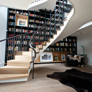 This is an example of an expansive contemporary wood curved staircase in Kent with wood risers.