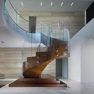 Immagine di una scala a chiocciola design con alzata in legno, pedata in legno e parapetto in vetro
