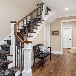 Cette photo montre un grand escalier chic en L avec des marches en bois peint, des contremarches en moquette et un garde-corps en matériaux mixtes.