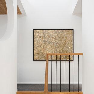 """Ispirazione per una scala a """"U"""" industriale di medie dimensioni con pedata in legno, nessuna alzata e parapetto in legno"""