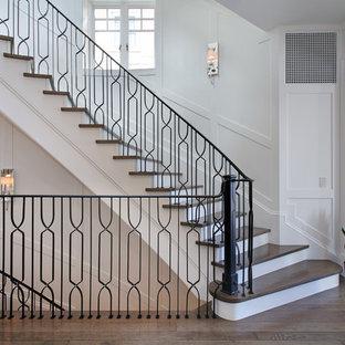 Ejemplo de escalera curva, clásica renovada, grande, con escalones de madera y contrahuellas de madera pintada