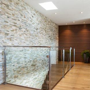Idee per una scala a rampa dritta minimalista di medie dimensioni con pedata in legno, alzata in legno e parapetto in vetro