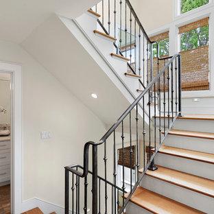 Modelo de escalera curva, tradicional renovada, de tamaño medio, con escalones de madera y contrahuellas de metal
