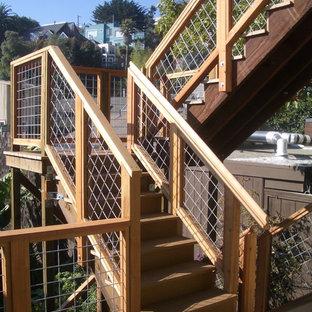 オレンジカウンティの中サイズの木のトロピカルスタイルのおしゃれなかね折れ階段 (木の蹴込み板) の写真