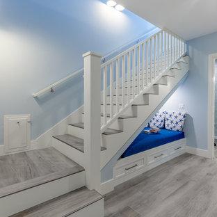 サンディエゴのタイルのビーチスタイルのおしゃれなかね折れ階段 (フローリングの蹴込み板、木材の手すり) の写真