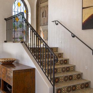 Foto de escalera recta, mediterránea, pequeña, con contrahuellas con baldosas y/o azulejos, barandilla de metal y escalones con baldosas