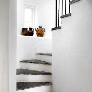 ロンドンの中サイズのスレートの地中海スタイルのおしゃれな階段 (金属の手すり) の写真