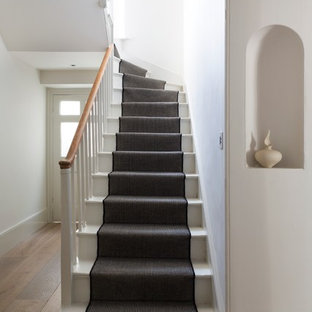 This is an example of a victorian painted wood l-shaped staircase in Oxfordshire with painted wood risers.