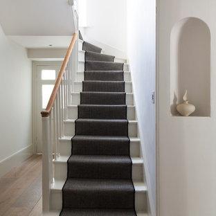 На фото: угловые лестницы в викторианском стиле с крашенными деревянными ступенями и крашенными деревянными подступенками