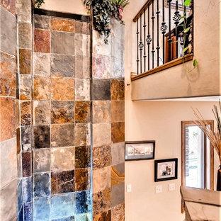 Diseño de escalera curva y boiserie, de estilo americano, grande, con escalones de madera, contrahuellas de pizarra, barandilla de madera y boiserie