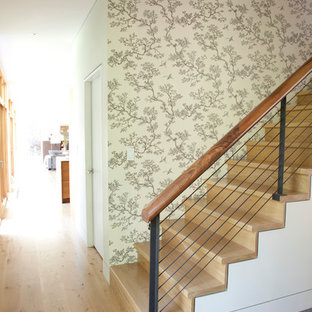 Design ideas for a contemporary wood staircase in New York with wood risers and cable railing.