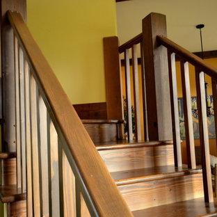 Ejemplo de escalera curva, campestre, pequeña, con escalones de madera y contrahuellas de madera