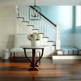 Diseño de escalera en U, costera, grande, con barandilla de madera, escalones de madera y contrahuellas de madera pintada