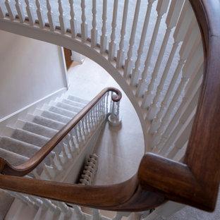 Imagen de escalera curva, actual, grande, con escalones enmoquetados, contrahuellas enmoquetadas y barandilla de madera