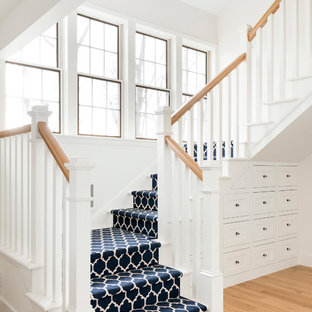 Country carpeted u-shaped wood railing staircase photo in Minneapolis