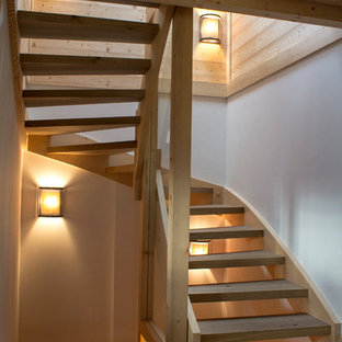 Photo of a farmhouse wood curved wood railing staircase in Other with open risers.