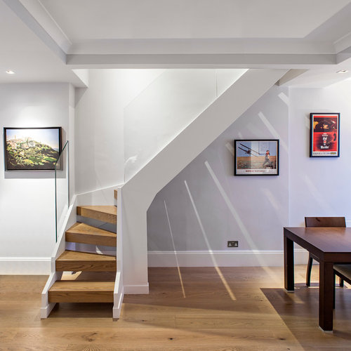 Trendy glass railing staircase photo in London Open Basement Stair  Houzz