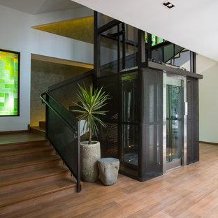 Diseño de escalera en L, actual, con escalones de madera, contrahuellas de madera y barandilla de metal