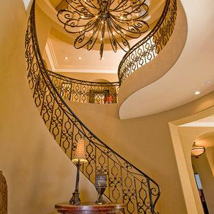 オレンジカウンティの広いカーペット敷きの地中海スタイルのおしゃれならせん階段 (カーペット張りの蹴込み板) の写真