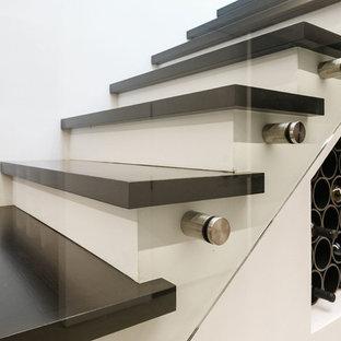Foto de escalera en L, bohemia, con escalones de madera pintada, contrahuellas de madera pintada y barandilla de vidrio