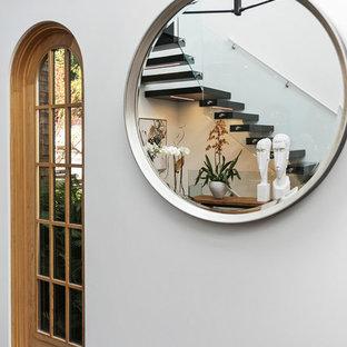 Modelo de escalera suspendida, bohemia, con escalones de madera pintada, contrahuellas de madera pintada y barandilla de vidrio