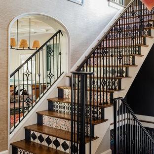 Diseño de escalera en U, bohemia, con escalones de madera, contrahuellas con baldosas y/o azulejos y barandilla de metal