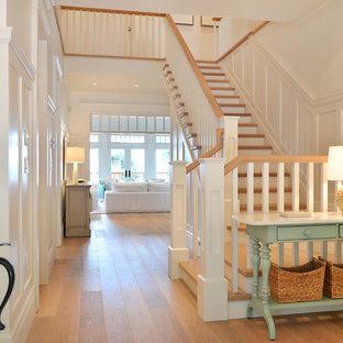 Пример оригинального дизайна интерьера: угловая лестница в морском стиле с деревянными ступенями и крашенными деревянными подступенками