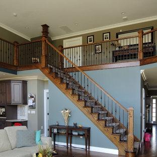 Ejemplo de escalera recta, de estilo americano, grande, con barandilla de varios materiales, escalones de madera y contrahuellas de madera