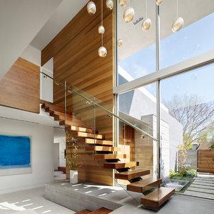 Ispirazione per una scala sospesa minimal di medie dimensioni con pedata in legno, parapetto in metallo e nessuna alzata