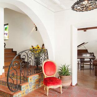 На фото: угловая лестница в средиземноморском стиле с подступенками из плитки, ступенями из терракотовой плитки и металлическими перилами с