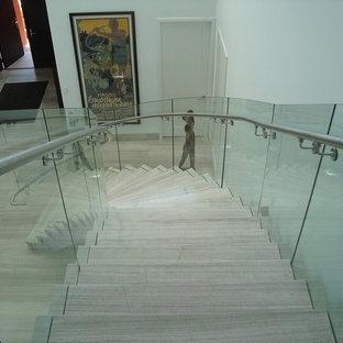 Foto de escalera curva, moderna, de tamaño medio, con barandilla de vidrio y escalones de madera
